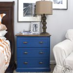 IKEA RAST Makeover blue dresser with hardwood top, glass lamp, and wall photos