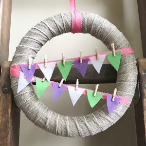 Burlap ribbon wrapped wreath with colorful bunting held on with mini clothes pins