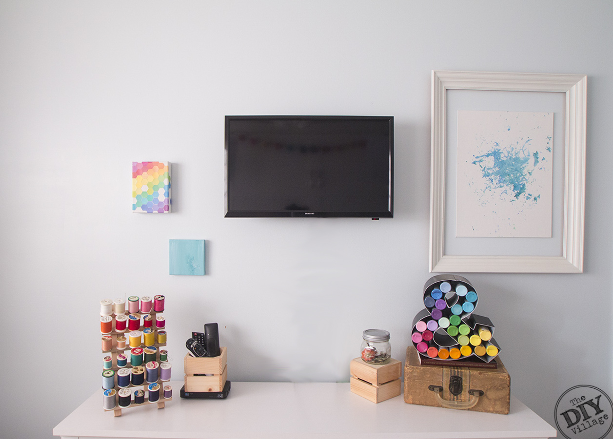 wall with art, tv, colorful thread, craft paints, craft room